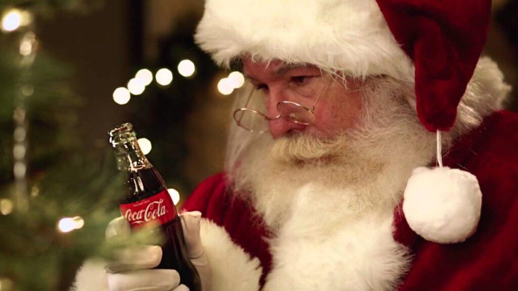 djed božićnjak gleda u boćicu coca-cole