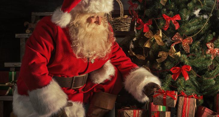 djed božićnjak sotavlja poklone ispod bora